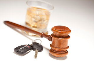 Drunken driving case illustrated by a drink, keys and gavel.
