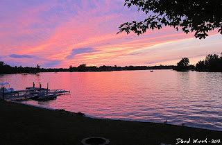 sunset by lake, red and pink sky at sunset, clouds in water, boat on cottage lake