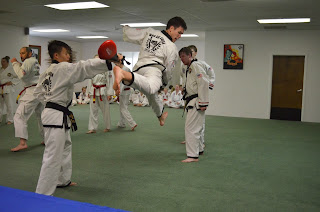 A martial arts black belt doing a jump back kick while learning martial arts
