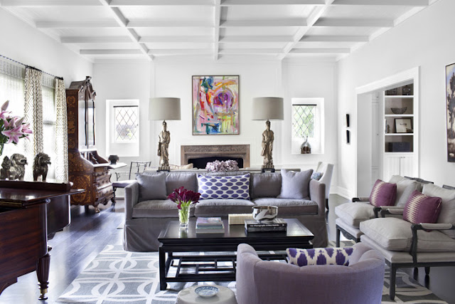 Living room in Tudor style home with gray sofas with purple accent pillows, statuette lamps and a piano