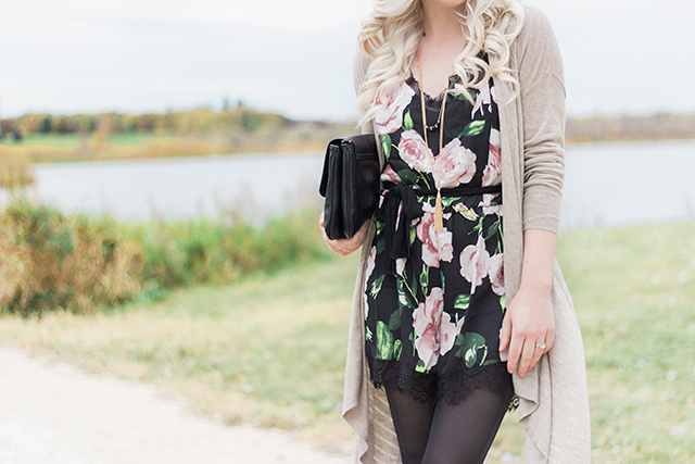 Black and pink floral romper with a cozy cardigan for fall.