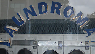 "Photo of a window showing peeling letters spelling ""laundromat""."