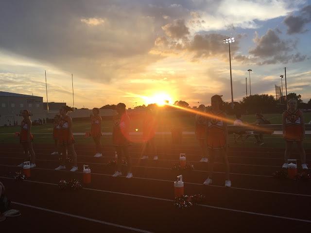 Soleil couchant, contre-jour laissant deviner une équipe de cheerleaders devant un terrain de foot US.