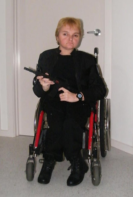 Kellie, in a wheelchair, dressed up in a costume, holding a gun