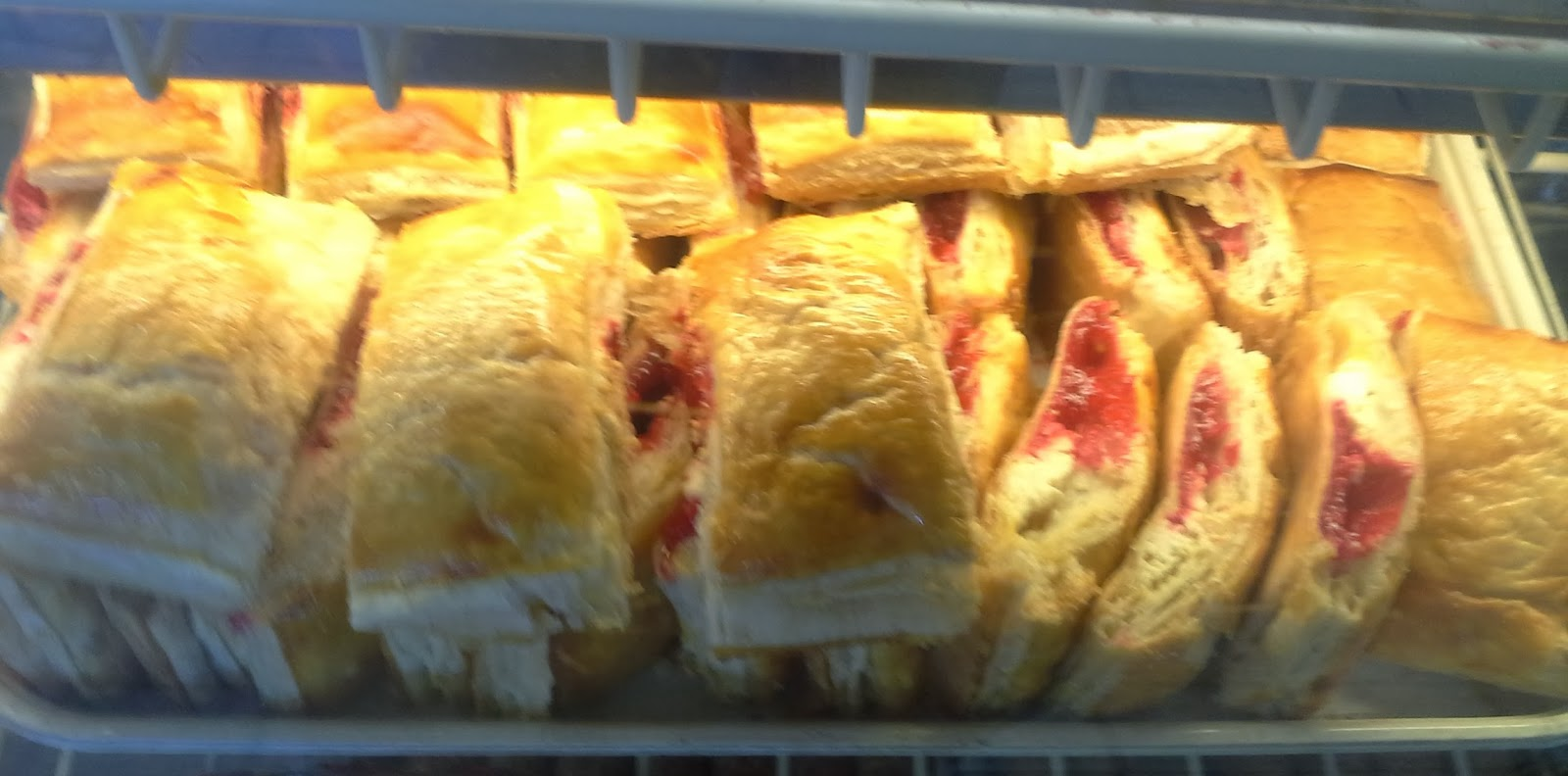 the baker layers guava paste and cream cheese on one long layer of of ...