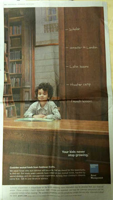 Full page ad showing an elementary-age boy sitting at a library table surrounded by dark paneling and leather books, with Goldman Sachs logo in lower right
