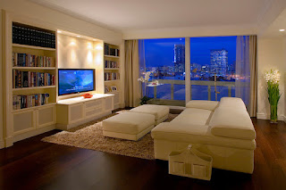 Amazing White Modern Sofa Bed in the TV Room with White Bookshelves and Brown Rug on Wooden Floor