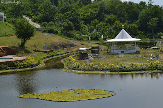 the white gazebo in the middle of the man made pond