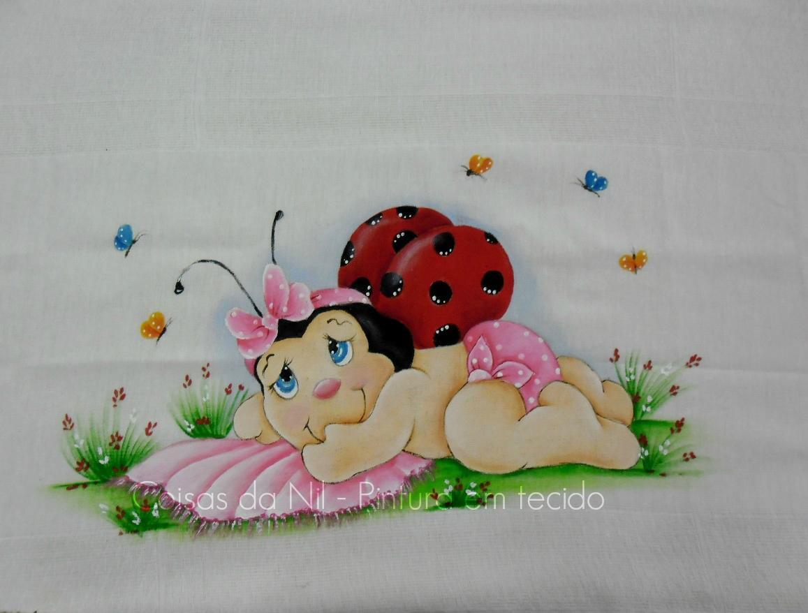 fralda pintada com joaninha baby deitada sobre uma manta rosa
