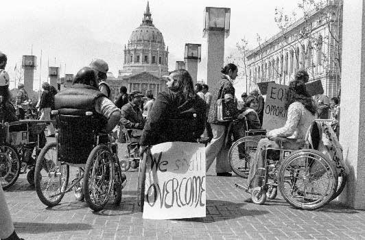 "A diverse crowd of people with disabilities gathers in front of the HEW building, city hall can be seen in the distance, a sign reads ""We Shall Overcome."""