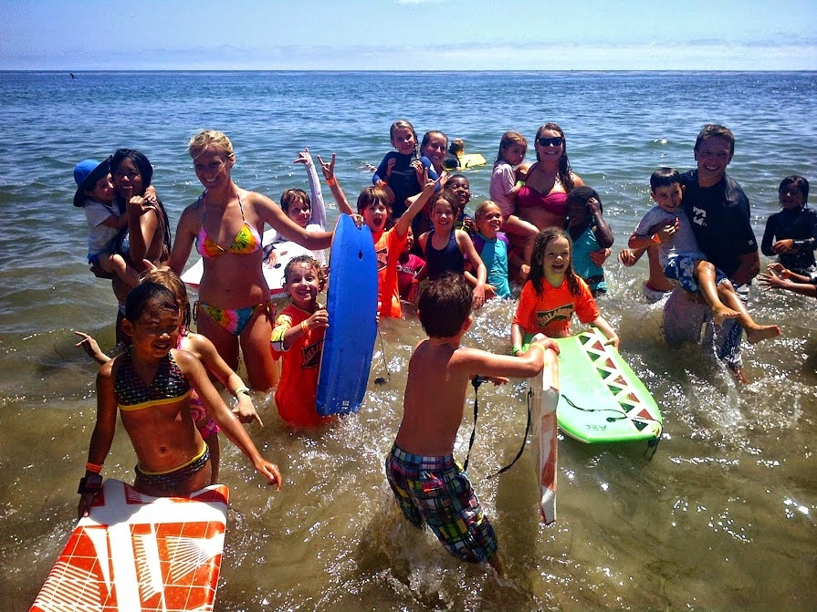 Aloha Beach Camp kids and their camp counselors playing in the ocean at Zuma Beach. Kids and teens who live in the Larchmont area of Los Angeles can enjoy a beach camp experience just like this when signing up for camp this summer. Aloha Beach Camp is providing free daily transportation to and from camp with a convenient bus stop at Third Street School in Hancock Park, just minutes from the Larchmont area.
