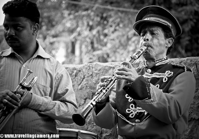 Recently I attended my friend's marriage in Himachal. I was the first one to reach early and other friends were on the way... So had a good opportunities to see various things happening around and of course, there was hardly any other choice :) ... So I was listening to this band group. In Himachal band-group arrives one day before the barat day and they play during most of the ceremonies happen during the marriage. So every 30-45 minutes, they were playing various things like Aartis, Bollywood numbers, local folk etc. Usually in these band there is  leader who starts the song with a different music and other carry on further. The person in photograph is band-master who starts and guide through a song. You can notice the other person on left who is not playing anything right now. So he is just listening to the music his master is playing and then all of them will continue. While is proper mood, they do various experiments with songs we listen to. And many times these folk tunes are used by big composers in Bollywood !!!