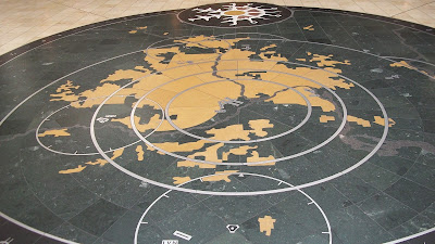 A map laid out in tile on the floor of the airport, at a junction between two major walkways.