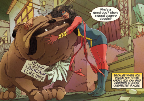 A single comics panel. Lockjaw, a massive bulldog with a tuning fork on his hand, stands still with his chin upraised so a brown girl in a blue, red, and gold superhero costume can hug him. She says, 'Who's a good dog? Who's a good bizarro doggie?' A caption to the right reads, 'Because when you decide not to be afraid, you can find friends in super unexpected places.' Lockjaw wears a sign around his neck. It reads 'Hello my name is Lockjaw I like hugs.'