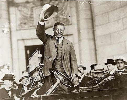 Roosevelt waving from car, 1909