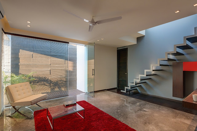 Picture of the entrance room with the staircase, red carpet and white chair