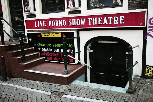 "A theatre sign in the Amsterdam Red Light District that says, ""Live Porno Show Theatre""."