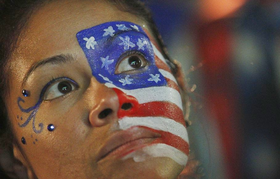 A fan of the U.S. national soccer team, with her face painted with the nation's colors watches her team's World Cup round of 16 match against Belgium on a live telecast inside the FIFA Fan Fest area on Copacabana beach in Rio de Janeiro, Brazil, Tuesday, July 1, 2014. Belgium beat the United States 2-1 in extra time to reach World Cup quarterfinals.