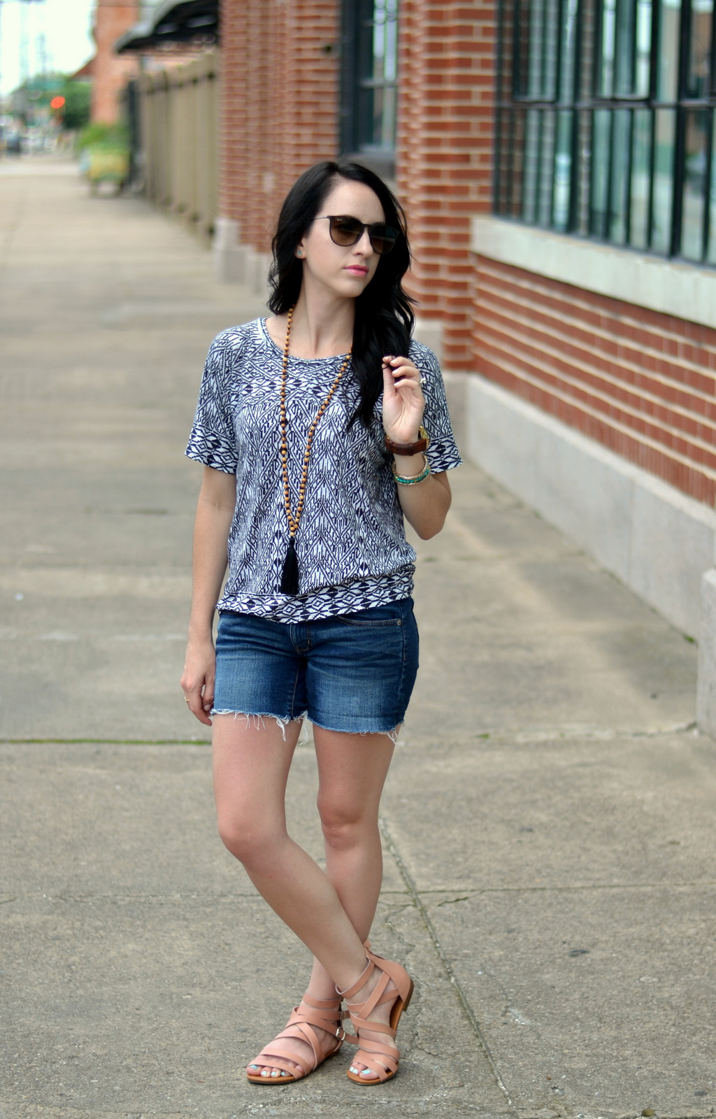 Cut-off denim shorts, patterned tee, tassel necklace