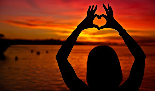 Girl holding up fingers to make a heart shape into sunset