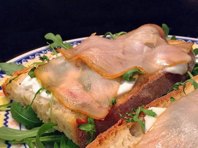 I crostoni con spada affumicato, rucola e bufala sono un antipasto dal sapore intenso ma elegante.