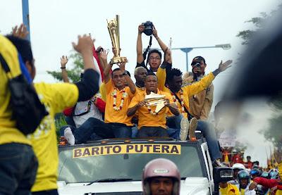 Para pemain Barito diatas Mobil sambil mengangkat piala