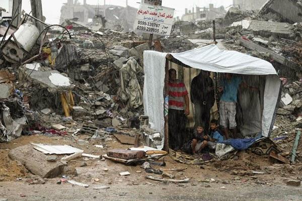 Warga Palestina berlindung dari hujan di depan tenda buatan dekat reruntuhan rumah mereka yang menurut saksi mata hancur dalam serangan tujuh minggu Israel, di timur Kota Gaza