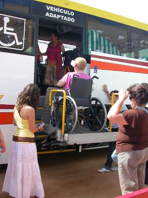 Viajera en silla de ruedas accede a autobús discrecional por la entrada para usuarios de sillas de ruedas.