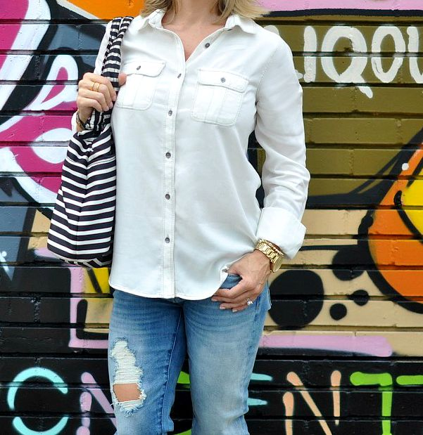 Fall fashion - distressed jeans and white button down with striped bag
