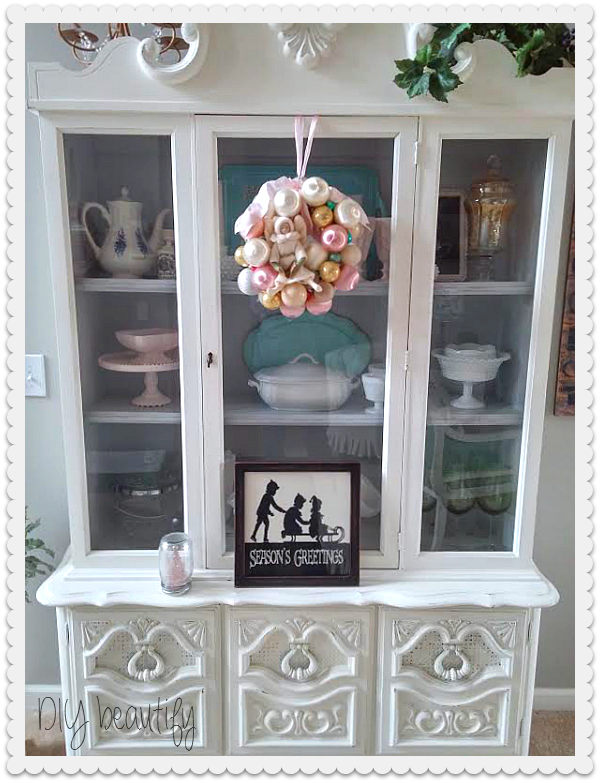 White hutch decorated for Christmas at www.diybeautify.com
