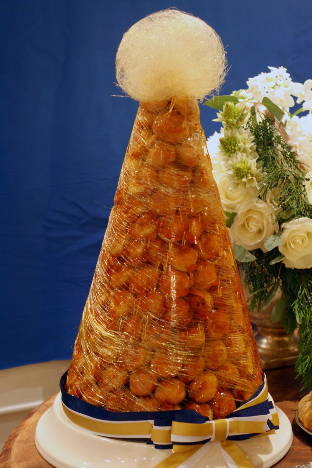A mountain of Croquembouche wrapped in spun golden sugar threads.