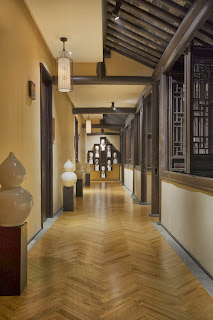 chevron patterned floor, ceramicgourds and white face sculptures welcomes on entryway