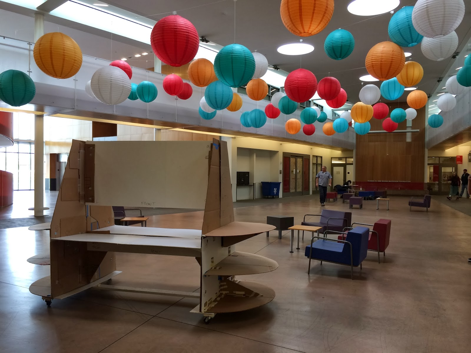 A full scale exhibit display made of cardboard stands inside the Ed Roberts Campus while a variety of colored circular paper lanterns hang from the ceiling.