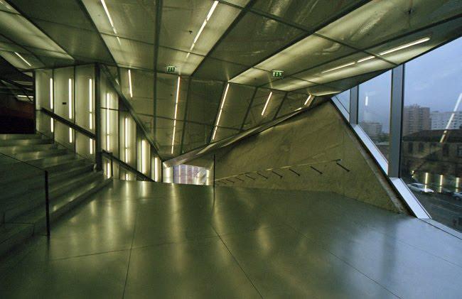 Pormenor de um patamar entre escadarias com muitos ângulos e reflexos nas superfícies metálicas originando grafismos que se assemelham a estruturas cristalinas