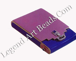 This Art Deco compact of 1927, with a design of diamonds, has a cabochon sapphire on a surface of pink and violet enamel on gold.