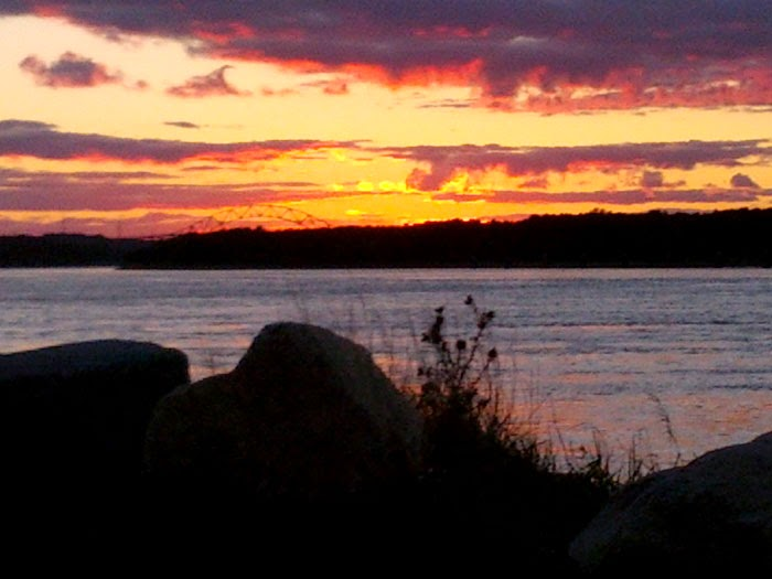pink and yellow sky over water of Cape Cod Canal
