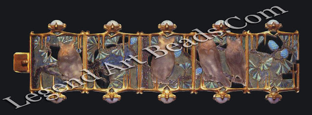An owls bracelet of gold, chalcedony, enamel and glass (c. 1900-01), in which five plaques form a frieze of moulded frosted glass owls, each sitting on an enameled branch of a pine tree set against a moonlit sky of plique-a-jour enamel.
