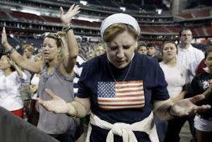 Seguidores de Rick Perry rezan en el transcurso de un mitin en Texas, el pasado 6 de agosto