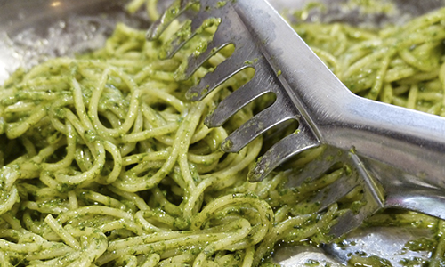 Healthy pesto pasta with a scooping utensil.
