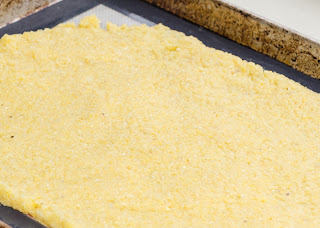 Cooked polenta spread out on a sheet pan