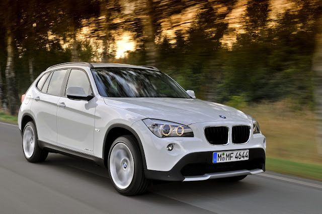 Front 3/4 view driving shot of white 2013 BMW X1