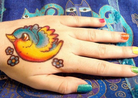Vivid colors little bird tattoo on hand
