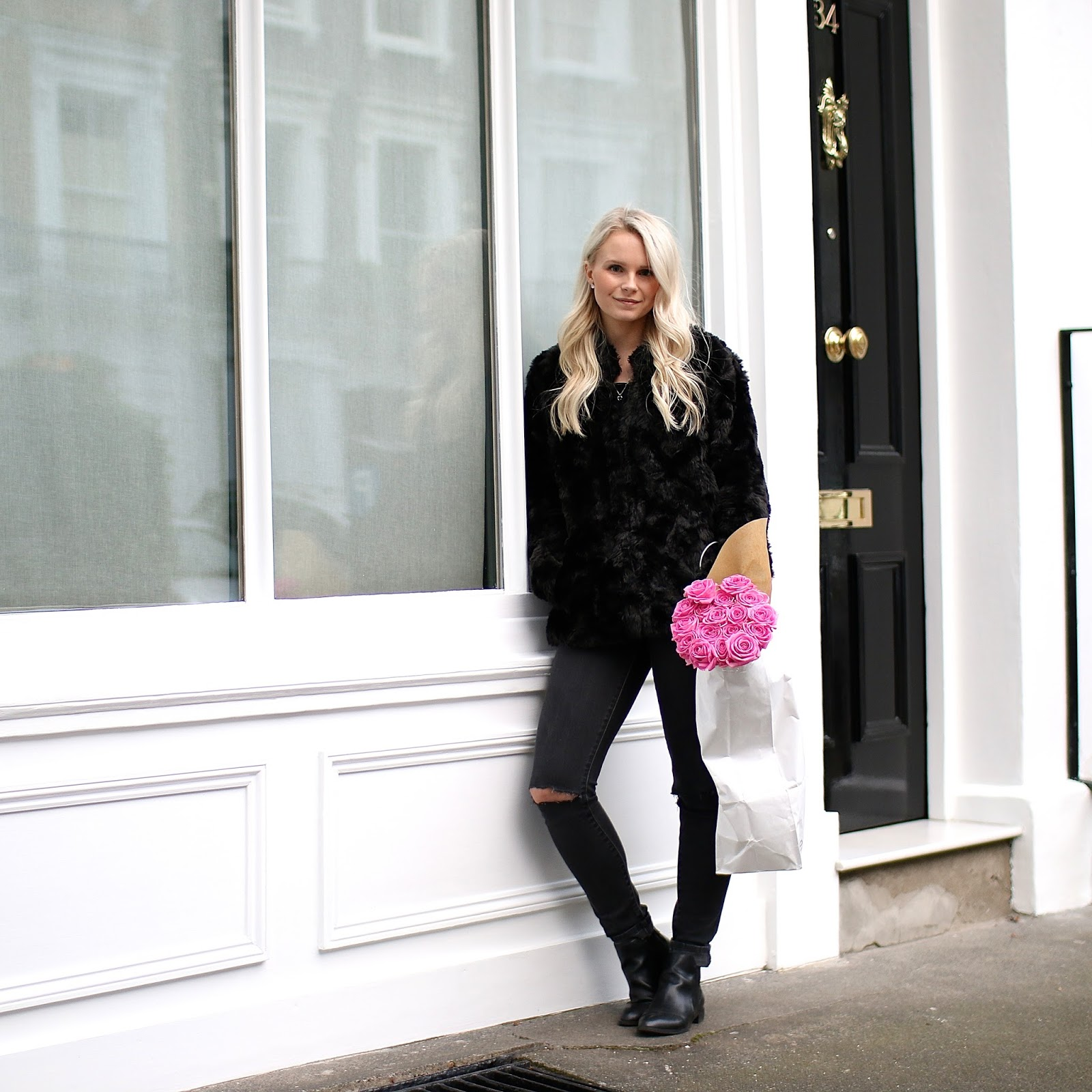 a women wearing an all black outfit and faux fur coat stands near portobello market with pink roses
