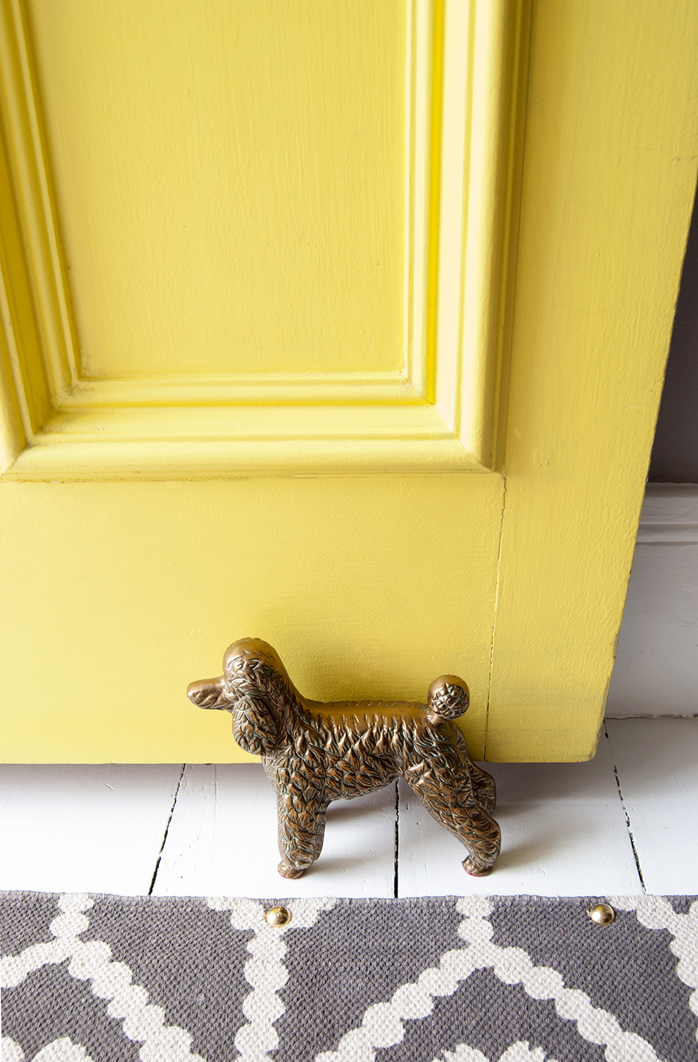 Brass poodle doorstop in front of yellow door with white painted floorboards and rug