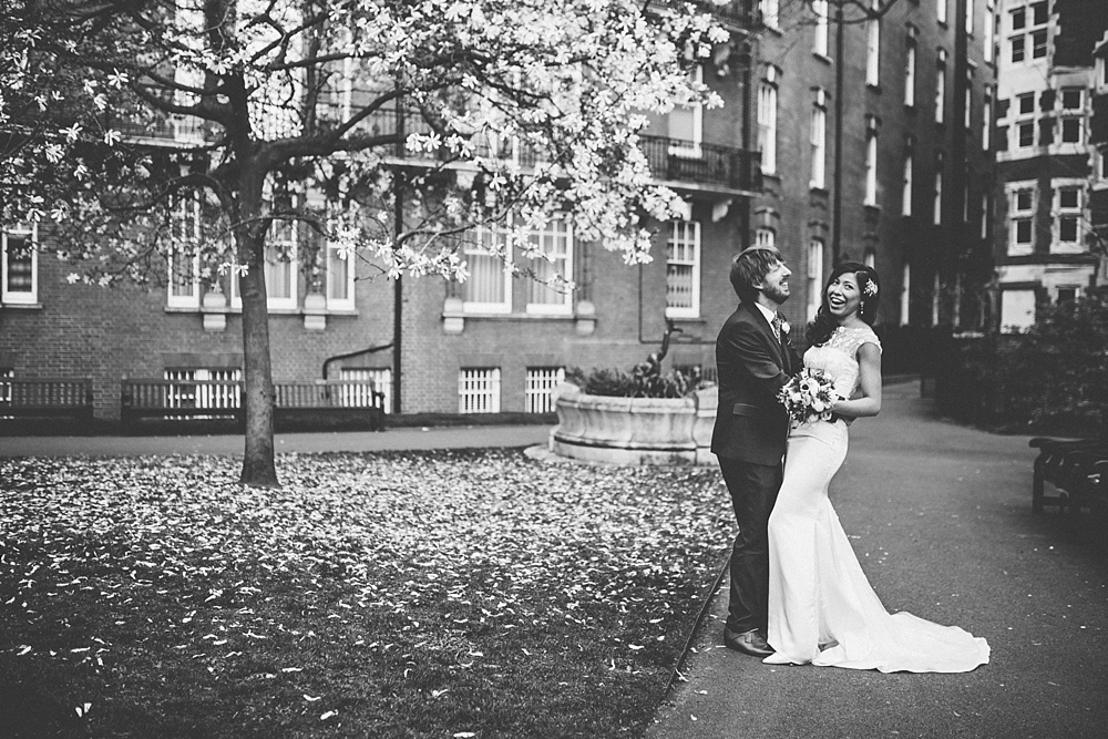 couple laughing during couples portraits for their wedding photography in london park