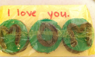 "picture of cookies wrapped on an index card that reads ""I love you"". The cookies spell out M-O-M."