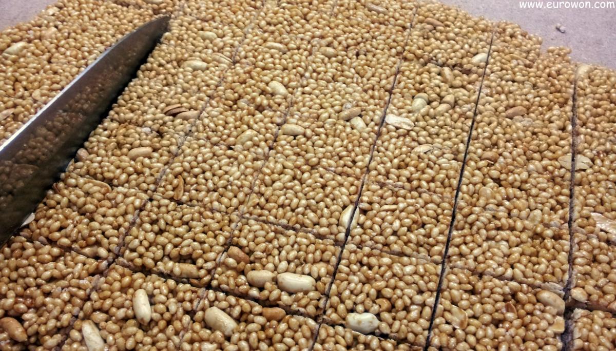 Cortando gangjeong de arroz inflado y cacahuetes