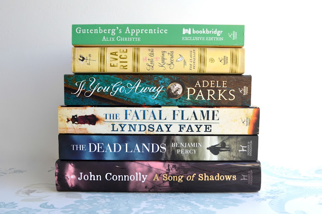 A pile of books including Gutenberg's Apprentice by Alix Christie, The Lost Art of Keeping Secrets by Eva Rice, If you go Away by Adele Parks, The Fatal Flame by Lindsay Faye, The Dead Lands by Benjamin Percy and A Song of Shadows by John Connolly