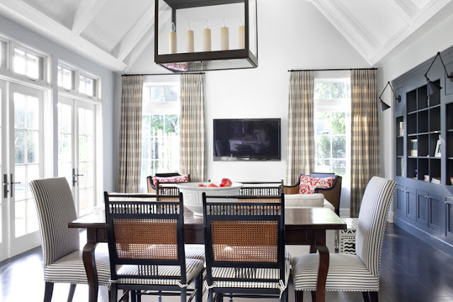 Dining room in a Tudor style home in Beverly Hills with cane back chairs, Parson's chairs and French doors