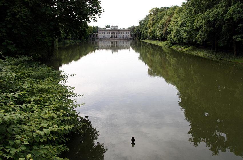 Foto de um lago com as margens laterais preenchidas por plantas diversas e árvores de grande porte e ao fundo o palácio com o seu reflexo na água